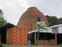 A family run brickworks in the Mekong Delta. Bricks are stacked in front and the beehive kiln - just like those used in Regency England, can be seen behind.