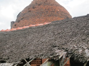 A Mekong Delta family run brick-works; the thatched brick storage are in the foreground and the beehive kiln behind.