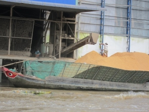 Lining the Mekong River are huge factories for preparing, bagging and transporting rice husks to be used for fuel